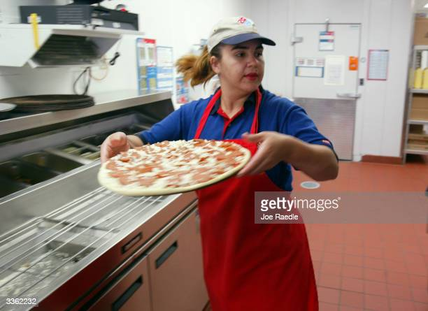 Gema Perez prepares a Domino's Pizza on April 14 2004 in Miami Florida Domino's Pizza is looking to raise $300 million in the stock market by listing...