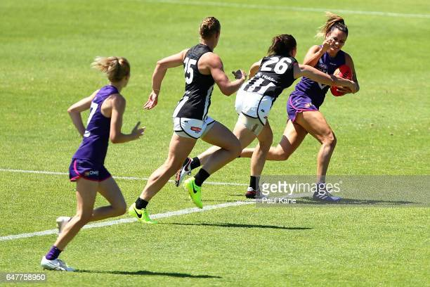 Gemma Houghton of the Dockers attempts to fend off a tackle by Tara Morgan of the Magpies during the round five AFL Women's match between the...