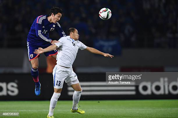 Gen Shoji of Japan competes for the ball against Lutfulla Turaev of Uzbekistan during the international friendly match between Japan and Uzbekistan...
