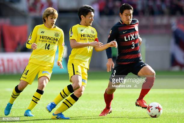 Gen Shoji of Kashima Antlers controls the ball under pressure of Hidekazu Otani and Junya Ito of Kashiwa Reysol during the JLeague J1 match between...