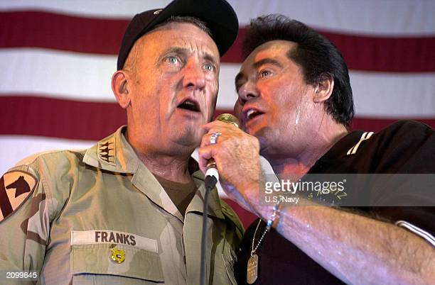 Gen Tommy Franks Commander of US Forces Central Command sings a duet with Wayne Newton aboard USS Nimitz during a United Services Organization show...