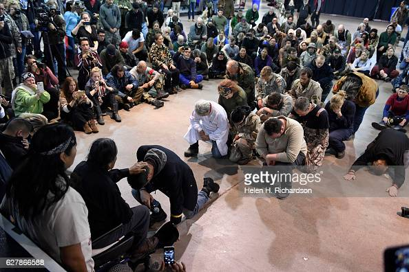 Gen Wesley Clark Jr kneels in front of Leonard Crow Dog left during a forgiveness ceremony at the Four Prairie Knights Casino Resort on the Standing...