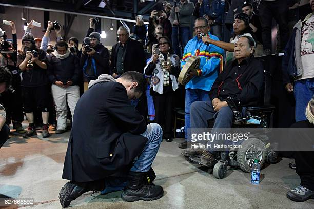 Gen Wesley Clark Jr left kneels in front of Leonard Crow Dog right during a forgiveness ceremony at the Four Prairie Knights Casino Resort on the...