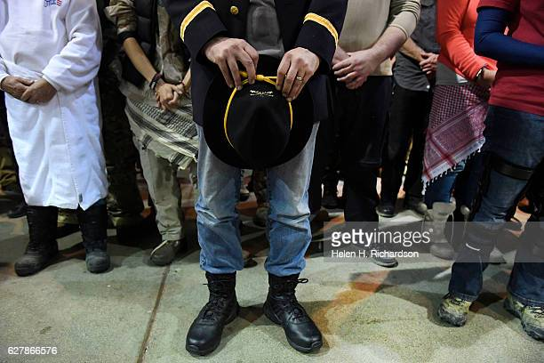 Gen Wesley Clark Jr middle holds his calvary hat in prayer during an emotional forgiveness ceremony at the Four Prairie Knights Casino Resort on the...