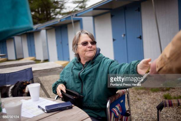 Gena Kilkenny takes money from a vendor the opening morning of Montsweag Flea Market The market which sits in a field near her family home was...