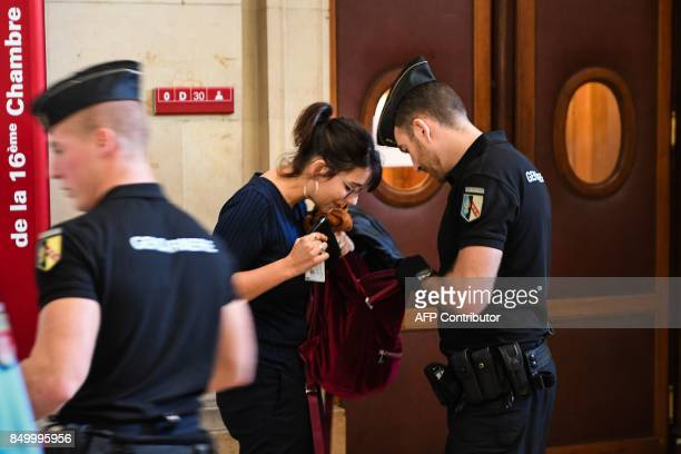 A gendarme checks a woman's bag as while controlling access to enter the 16th courtroom on September 20 2017 at the Paris courthouse prior to the...