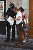 A gendarme or police officer assists two lost tourists in Montmartre Paris France circa 1965
