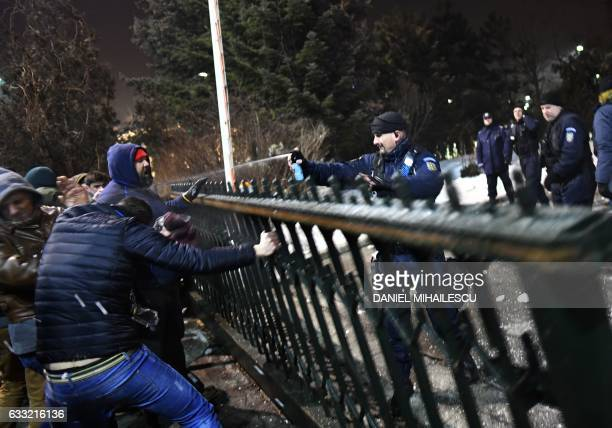 TOPSHOT A gendarme pepper sprays demonstrators forcing entrance to government headquarters as they demonstrate against controversial decrees to...