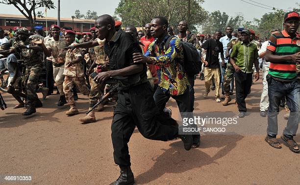 A gendarme runs away from members of the Central African Armed Forces who is suspected of being a former Seleka rebel on February 5 in Bangui as a...