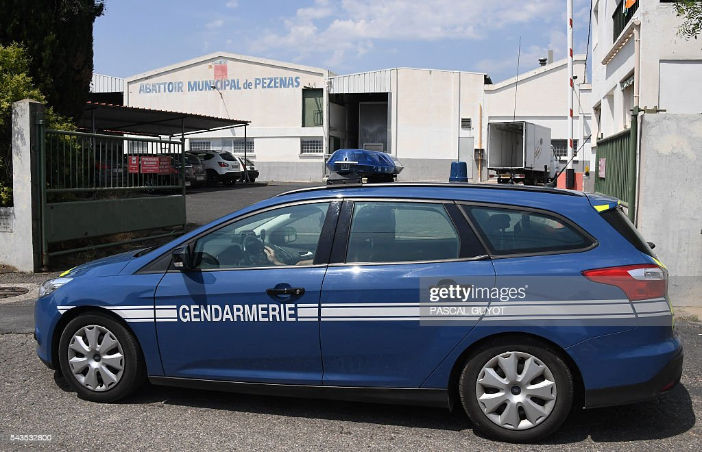 A gendarme sits in a car parked in front of the municipal slaughterhouse of Pezenas, on June 29, 2016 after the L214 association released a video denouncing poor animal handling methods in two southern France's slaughterhouses in Pezenas and Puget-Theniers. GUYOT