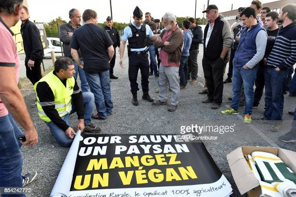 A gendarme talks ta a protester during a counter protest of livestock farmers as part of an action called by the Rural Coordination farmers union...