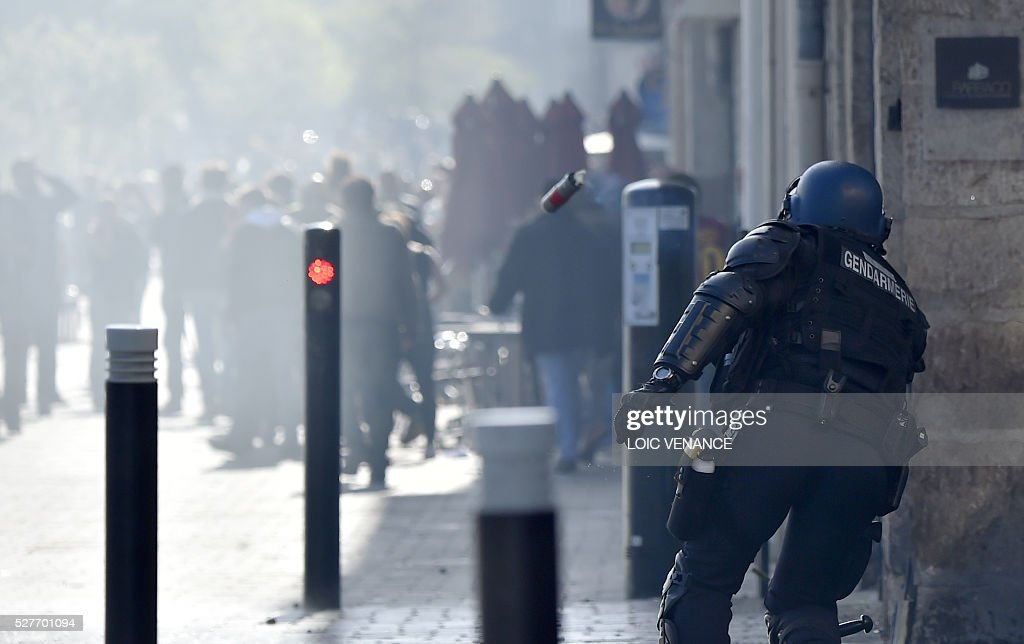 A gendarme throws a tear gas grenade to disperse a protest against the government's planned labour law reforms in Nantes, western France, on May 3, 2016. High school pupils and workers protested against deeply unpopular labour reforms that have divided the Socialist government and raised hackles in a country accustomed to iron-clad job security. / AFP / LOIC
