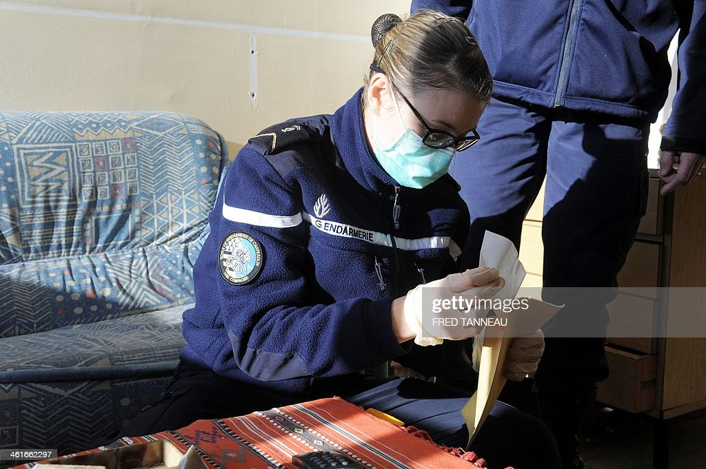 A Gendarme trainee collects evidence at a mock crime scene in the Gendarmerie school in Dineault, western France, on January 10, 2014.