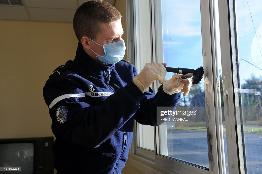 A Gendarme trainee dusts for fingerprints at a mock crime scene in the Gendarmerie school in Dineault, western France, on January 10, 2014.
