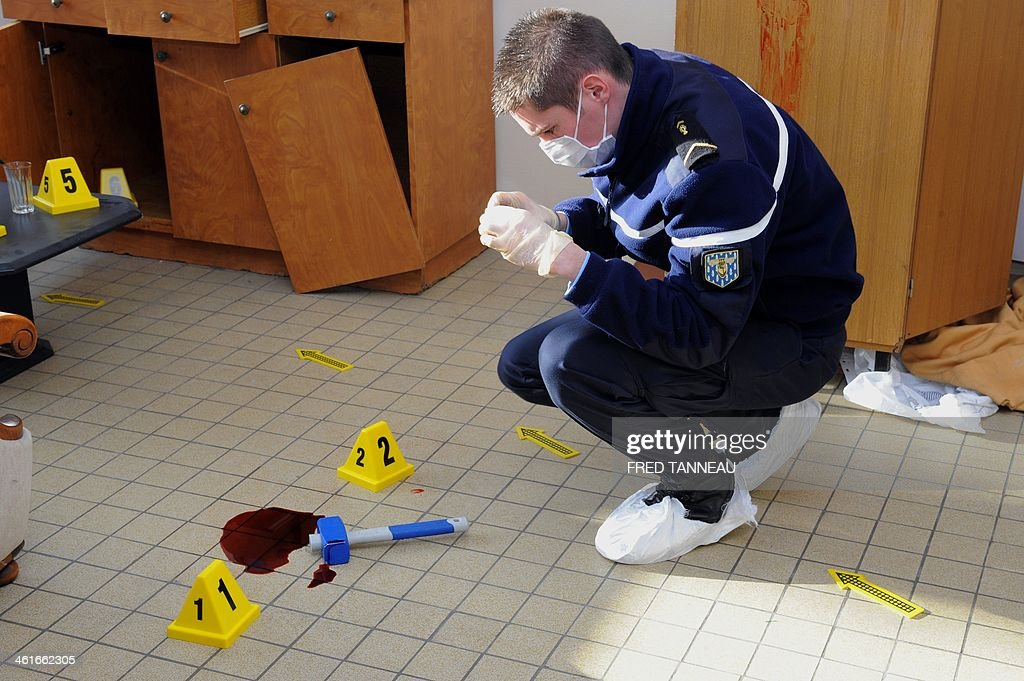 A Gendarme trainee takes pictures at a mock crime scene in the Gendarmerie school in Dineault, western France, on January 10, 2014.