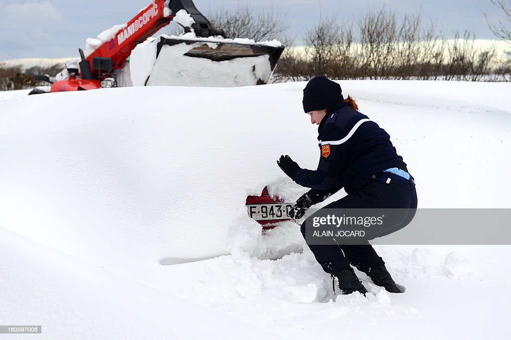 A gendarme wipes the snow off a car's registration plate on March 13, 2013, on the D901 (secondary road 901) near Beaumont-Hague, northwestern France. More than 68,000 homes were without electricity in France and hundreds of people were trapped in their cars after a winter storm hit with heavy snow, officials and weather services said on March 12. Twenty-six regions in northwest and northern France were put on orange alert because of heavy snowfalls, which Meteo France said were 'remarkable for the season because of the expected quantity and length of time'. AFP PHOTO/ ALAIN JOCARD