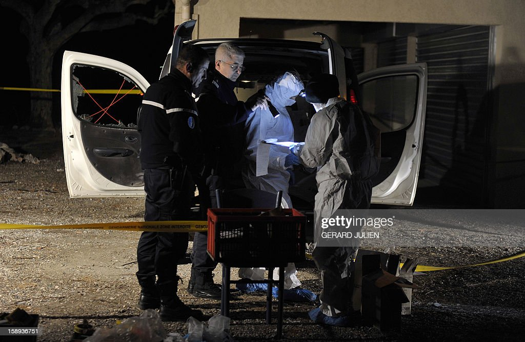 Gendarmes and forensic officers investigate at night near the vehicle where a man was shot dead earlier in front of his restaurant, on January 3, 2013 in Trets, near Aix-en-Provence in southeastern France.