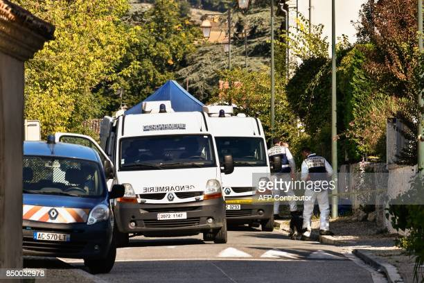 Gendarmes and search dogs stand outside a house searched by police forces in Nerac southwestern France on September 20 2017 in the investigation of...
