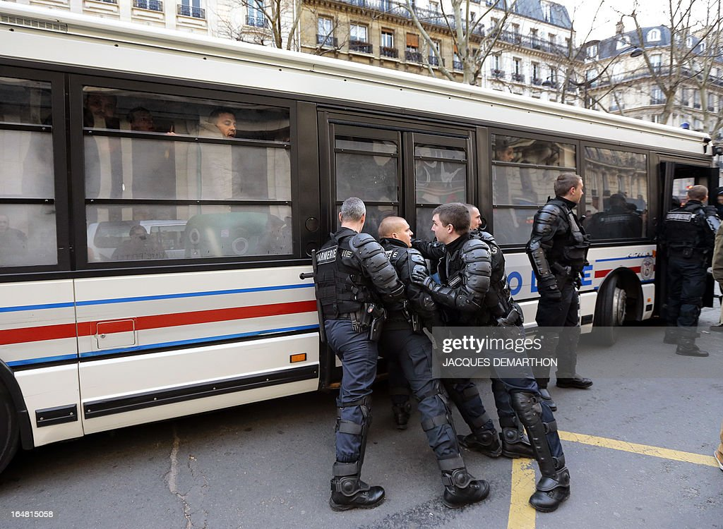 Gendarmes block the doors of a police bus where employees of French auto giant PSA Peugeot Citroen Aulnay are detained after a protest outside France's MEDEF employers' association headquarters on March 28, 2013 in Paris. About 150 PSA employees erupted earlier inside the MEDEF headquarters as they protested against the planned closure of their plant.