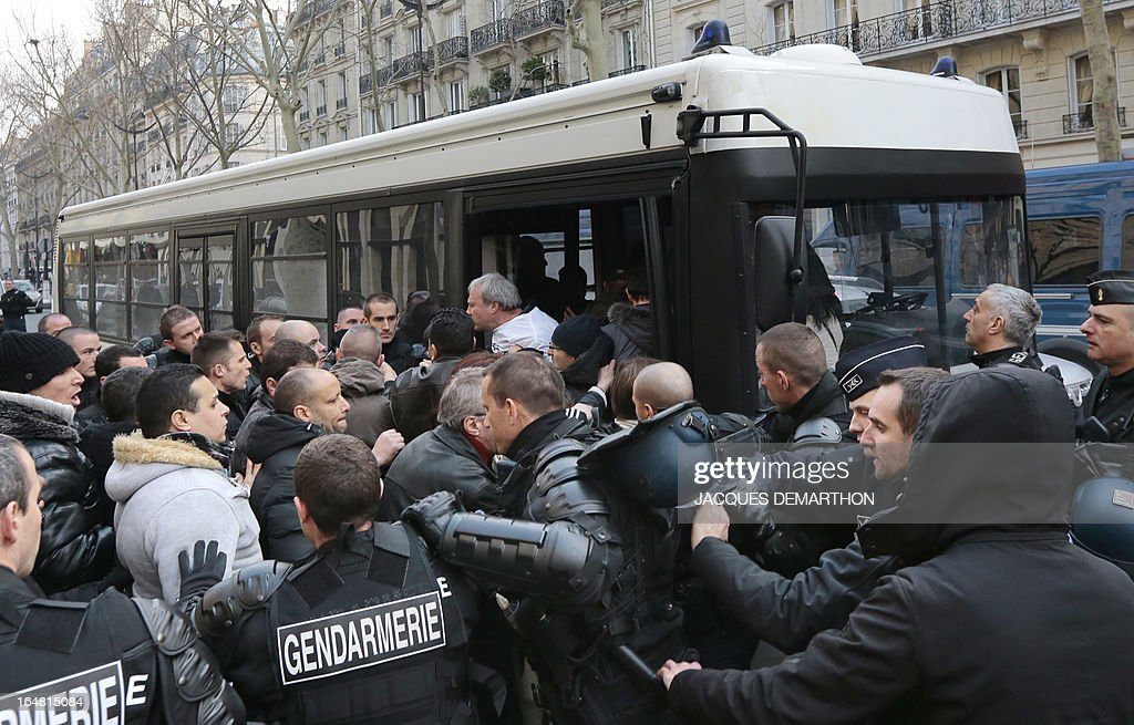 Gendarmes detain employees of French auto giant PSA Peugeot Citroen Aulnay into a police bus after a protest outside France's MEDEF employers' association headquarters on March 28, 2013 in Paris. About 150 PSA employees erupted earlier inside the MEDEF headquarters as they protested against the planned closure of their plant. AFP PHOTO / JACQUES DEMARTHON