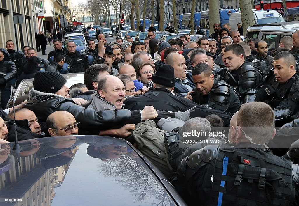 Gendarmes detain employees of French auto giant PSA Peugeot Citroen Aulnay into a police bus after a protest outside France's MEDEF employers' association headquarters on March 28, 2013 in Paris. About 150 PSA employees erupted earlier inside the MEDEF headquarters as they protested against the planned closure of their plant.