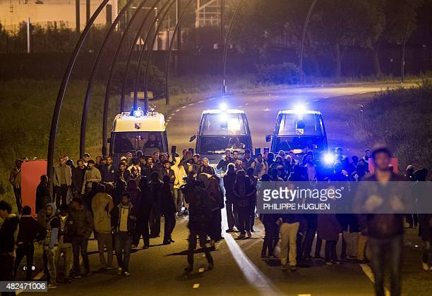 Gendarmes driving vans escort migrants out of the vicinity of the Eurotunnel terminal early on July 31 2015 in Coquelles near Calais northern France...