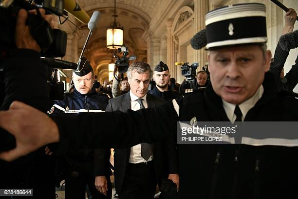 TOPSHOT Gendarmes escort French former budget minister Jerome Cahuzac as he leave the Paris courthouse following his tax fraud and money laundering...