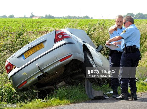 Gendarmes inspect a damaged car along a road on June 30 2013 in Godewaersvelde northern France following a traffic accident between two vehicles...