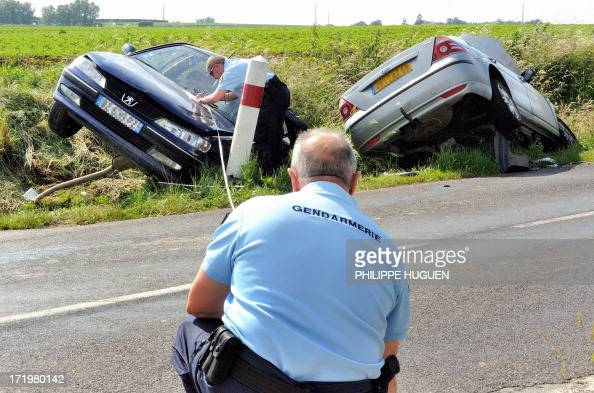 Gendarmes measure as they investigate near two damageds car along a road on June 30 2013 in Godewaersvelde northern France following a traffic...
