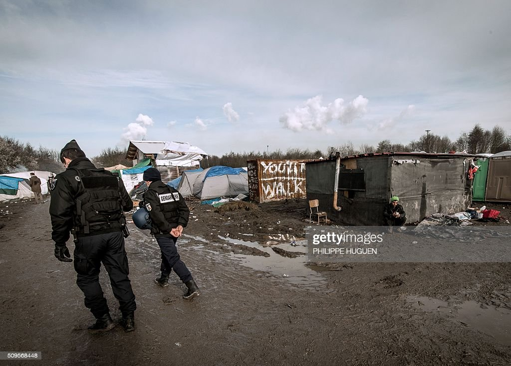 Gendarmes patrol in the so-called 'Jungle' migrant camp in Gande-Synthe where 2,500 refugees from Kurdistan, Iraq and Syria live on February 11, 2016 in Grande-Synthe near the city of Dunkirk, northern France. / AFP / PHILIPPE HUGUEN