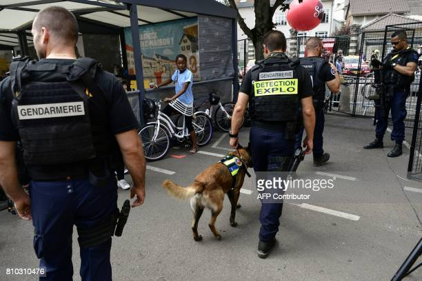Gendarmes patrol with their sniffer dog prior to the 2135 km seventh stage of the 104th edition of the Tour de France cycling race on July 7 2017...