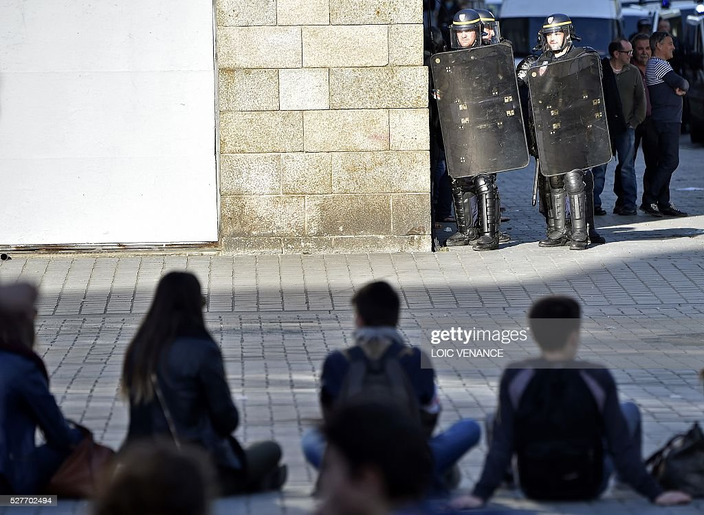 Gendarmes stand guard opposite demonstrators during a protest against the government's planned labour law reforms in Nantes, western France, on May 3, 2016. High school pupils and workers protested against deeply unpopular labour reforms that have divided the Socialist government and raised hackles in a country accustomed to iron-clad job security. / AFP / LOIC
