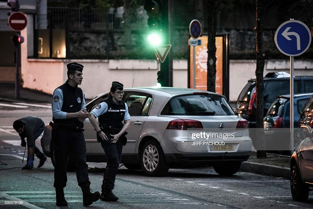 Gendarmes walk on May 29, 2016 in Tarare, near Lyon, central eastern France during the towing of a car belonging to a suspect after the murder of a mother of three. The woman was found dead on May 29 in Pontcharra-sur-Turdine, near Lyon. Her ex-husband, suspected of the murder, took their three children to his sister's house then surrendered to police. Earlier in the day the 'Plan Alerte Enlevement', for an abduction alert procedure, was triggered following the disparition of the children. / AFP / JEFF
