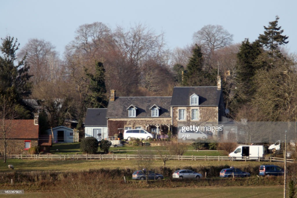 Gendarmes work around the alleged house where two bodies were found murdered on February 21, 2013 in the Normandy village of Perriers-en-Beauficel. An official explained that the alleged murderer has been located nearby the site and is actively searched by law enforcement.