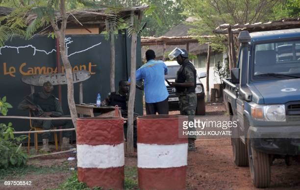 Gendarms stand at the entrance to the Kangaba tourist resort in Bamako on June 19 a day after suspected jihadists stormed the resort briefly seizing...