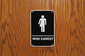 Gender neutral restroom sign on a wooden door that says, 'Who cares?'