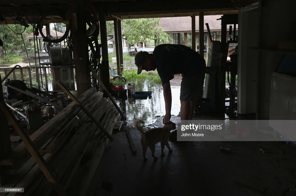 Gene Gibson pets his cat as water rises from the rising bayeux waters, flooding his property ahead of the arrival of Hurricane Isaac on August 28, 2012 in Bay St. Louis, Mississippi. Many residents of the area decided to stay in their homes instead of evacuate for the Level 1 hurricane. The area was devastated by Hurricane Katrina in 2005.