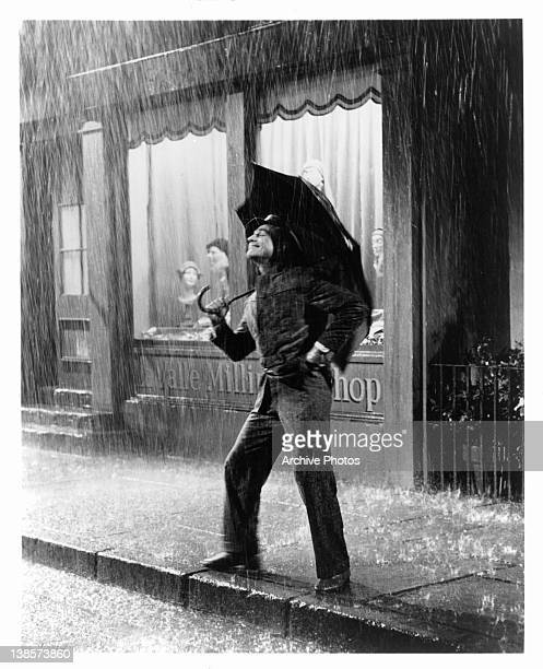 Gene Kelly standing out in the rain in a scene from the film 'Singin' In The Rain' 1952