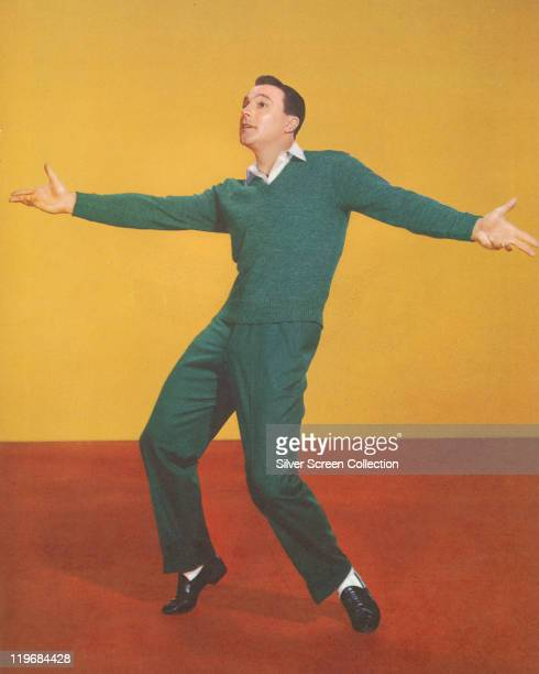 Gene Kelly US actor and dancer holding a dance pose in a studio portrait dancing on a red floor with a yellow wall in the background circa 1950