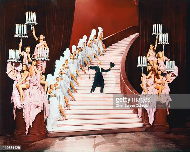 Gene Kelly US actor and dancer in top hat and tails dancing on a flight of stairs lined with dancing girls in costume in a publicity image issued for...