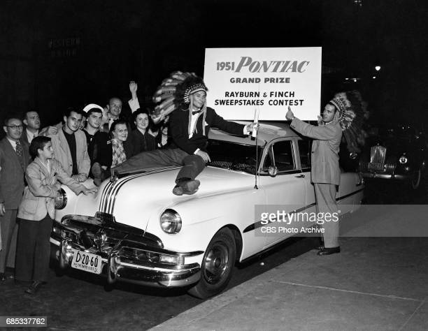Gene Rayburn and Dee Finch radio deejays of the 'Rayburn and Finch' morning drive time show in New York NY pose for a photo with a new 1951 Pontiac...