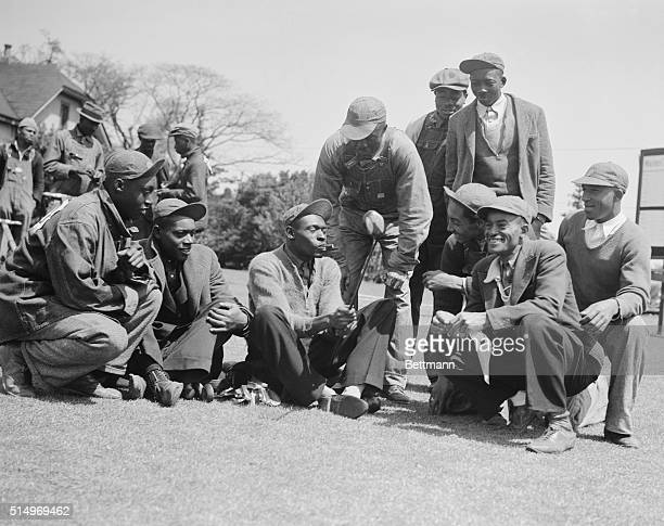 Gene Sarazen's favorite caddy Stovepipe is showing his fellow caddies the club with which Gene made the double eagle in 1935 Sarazen is among the...