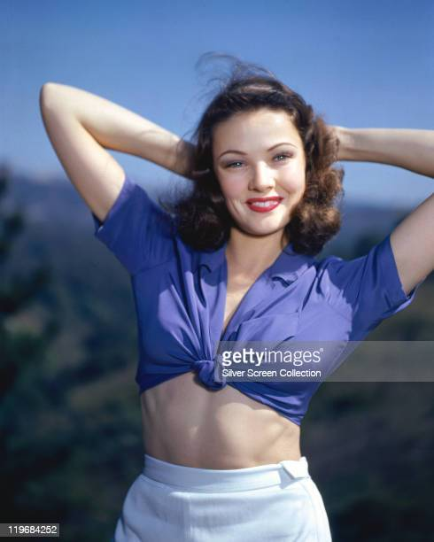 Gene Tierney US actress wearing a blue shortsleeved blouse tied around the waist with her arms behind her head circa 1940
