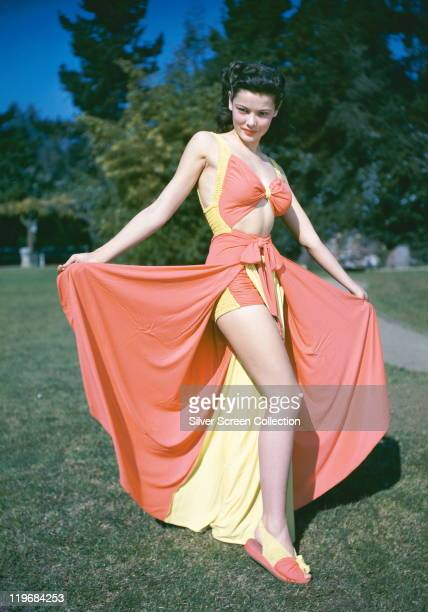 Gene Tierney US actress wearing a pinkandyellow bathing costume with a pinkandyellow sarong and matching slippers circa 1940