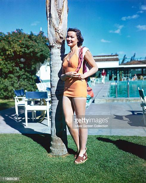 Gene Tierney US actress wearing an orange bathing costume posing beside a tree trunk circa 1940