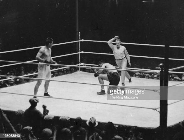 Gene Tunney looks on after he knocks down Jack Dempsey during the fight at Soldiers Field on September 221927 in Chicago Illinois Gene Tunney won by...
