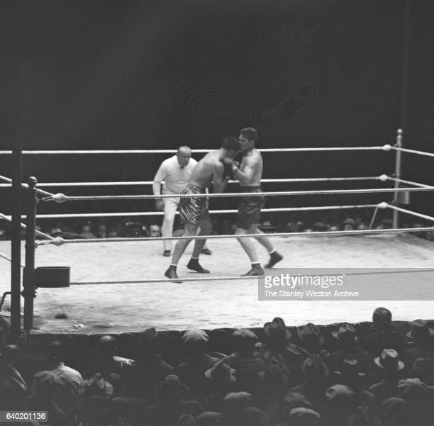 Gene Tunney throws a left hook to the head of Jack Dempsey as referee Tommy Reilly watches at Sesquicentennial Stadium Philadelphia Pennsylvania...