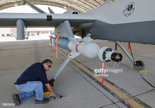 General Atomics Aeronautical Systems Inc airframe and power plant mechanic Michael Martinez inspects an inert training weapon on an MQ9 Reaper during...
