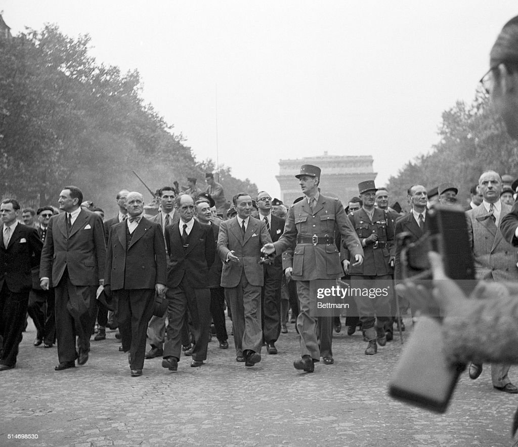 General Charles de Gaulle leads a triumphant procession down Champs-Elysees as part of the celebration of the liberation of Paris. To the right of de Gaulle is General Jacques-Philippe Leclerc, Commander of the French Armored Division.