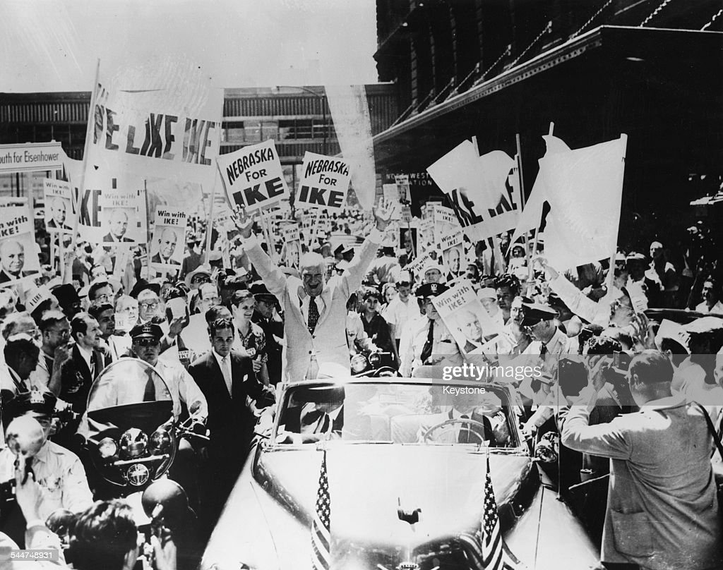 General Dwight Eisenhower raising his arms and smiling in the back of his car as he drives though the crowds of supporters holding 'We Like Ike'...